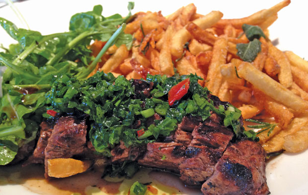 WHAT'SSOSPECIAL | A meaningless mesclun salad encroaches on the tough, chewy cut of steak with a banal chimichurri and woefully over-salted French fries. (Arnold Wayne Jones/Dallas Voice)